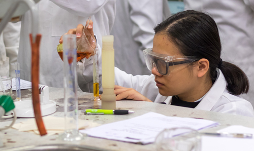 A student, wearing a white lab coat and safety googles, pours liquid from a beaker